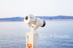 A telescope on the sea-summer, the sun, the sea, the beach. The inscription dream of the sea.  Royalty Free Stock Image