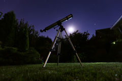 A telescope standing at backyard with night sky in the background. Astronomy and stars observing concept. A telescope standing at backyard with night sky in the royalty free stock photography