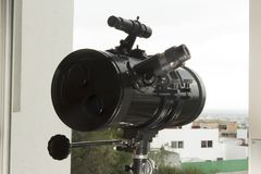 A telescope to observe neighborhood and sky. A telescope to spy the sky and the surroundings through a window Royalty Free Stock Photo