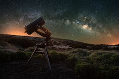 Telescope watching the Milky Way in the spring visible from Teide National Park near Observatory. Jupiter is sparkling surrounded. By star clusters and nebulae stock photo