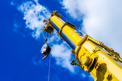 Telescopic arm of a mobile crane. Yellow telescopic arm of a mobile crane against deep blue sky and white clouds Royalty Free Stock Photos