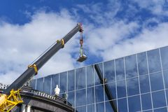 Crane lifts the load against the mirror wall of the building. Telescopic boom of a construction crane lifts the load against the mirror wall of the building royalty free stock photos