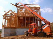 Telescopic Handler. Construction equipment with tall telescopic reach handing out roofing boards stock photography