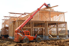 Telescopic Handler. Construction equipment with tall telescopic reach handing out roofing boards. Showing a 4-car garages side stock images
