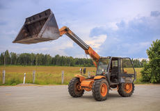 Telescopic Loader. Orange Telescopic Loader loading sawdust royalty free stock photography