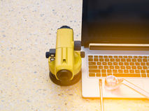 Telescopio, ordenadores portátiles y llave del ` s del topógrafo en piso Concepto del sector de la construcción fotos de archivo libres de regalías
