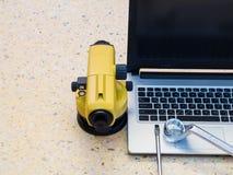 Telescopio, ordenadores portátiles y llave del ` s del topógrafo en piso Concepto del sector de la construcción fotos de archivo