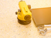Telescopio, ordenadores portátiles y llave del ` s del topógrafo en piso Concepto del sector de la construcción imagenes de archivo