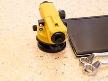 Telescopio, ordenadores portátiles y llave del ` s del topógrafo en piso Concepto del sector de la construcción imagen de archivo