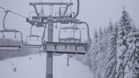 Telesilla vacía en montañas en las nevadas pesadas en el movimiento almacen de video