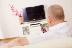 Telespettatore sul sofà con telecomando della TV Fotografie Stock Libere da Diritti