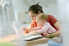 Teletrabajo de la mujer y cuidado el tomar de su bebé Fotografía de archivo libre de regalías