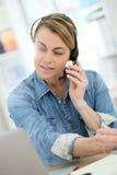 Teletrabajo de mediana edad de la mujer con los auriculares en el ordenador portátil Fotografía de archivo libre de regalías