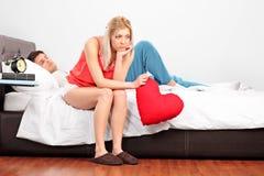 Teleurgesteld wijfje met hartzitting op een bed terwijl haar boyfri Royalty-vrije Stock Afbeeldingen