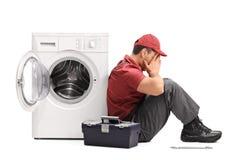 Teleurgestelde arbeiderszitting door een wasmachine Stock Foto