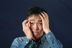 Teleurgestelde jonge Aziatische mens die camera bekijken stock foto's
