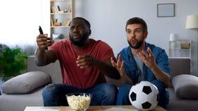 Teleurgestelde kerels die op voetbalwedstrijd letten die door nederlaag van favoriet team wordt gefrustreerd stock afbeeldingen