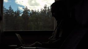 Teleurgestelde mens die aan een tablet in een trein werken stock footage