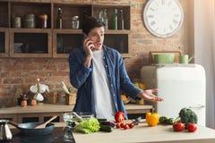 Teleurgestelde mens die gezond voedsel in de huiskeuken voorbereiden stock foto's