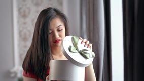Teleurgestelde mooie Aziatische vrouw die rode kleding het openen giftdoos dragen en het worden verstoord