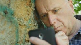 Teleurgestelde Persoon die aan Ongerust gemaakt en Hulpeloze Cellphone kijken royalty-vrije stock afbeeldingen