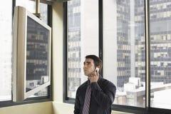 Televisão de Looking At Plasma do homem de negócios ao comunicar-se no telemóvel Imagens de Stock Royalty Free