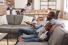 Televisão de observação de And Son Sit On Sofa In Lounge do pai foto de stock