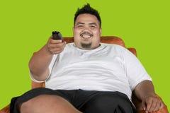 Televisão de observação do homem gordo feliz no estúdio imagem de stock