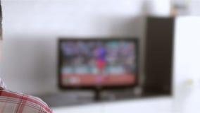 Televisão de observação do homem na sala de visitas vídeos de arquivo