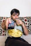 Televisão de observação do homem novo, comendo microplaquetas de batata e beber imagem de stock