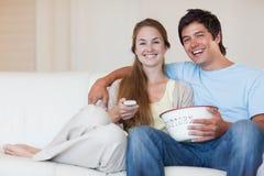 Televisão de observação dos pares ao comer a pipoca Imagens de Stock Royalty Free