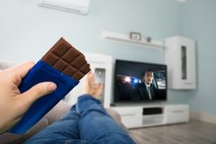 Televisão de Person Enjoying Chocolate While Watching imagem de stock