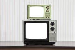 Televisões do vintage empilhadas na tabela com telas cortadas Foto de Stock