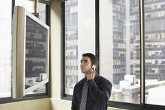 Televisión de Looking At Plasma del hombre de negocios mientras que comunica en el teléfono móvil Imágenes de archivo libres de regalías