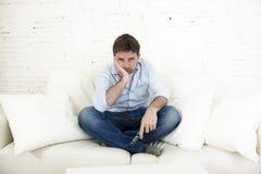 Televisión de observación agujereada del hombre que se sienta en el sofá que sostiene teledirigido cansado no divirtiéndose imagen de archivo libre de regalías