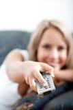 Televisión de observación de la mujer joven con un telecontrol Fotos de archivo