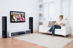Televisión de observación de la mujer mientras que se sienta en el sofá fotografía de archivo