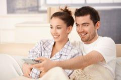 Televisión de observación de los pares felices en cama Fotos de archivo