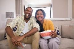Televisión de observación de los pares jovenes alegres mientras que se sienta en el sofá en casa foto de archivo