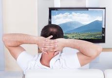 Televisión de observación del hombre en casa fotografía de archivo libre de regalías