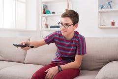 Televisión de observación del muchacho del adolescente, usando el control remoto de la TV Foto de archivo libre de regalías
