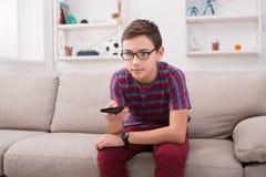 Televisión de observación del muchacho del adolescente, usando teledirigido Imagen de archivo