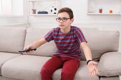 Televisión de observación del muchacho del adolescente, usando teledirigido Fotos de archivo libres de regalías