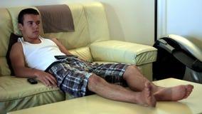 Televisión de observación del muchacho atractivo joven del adolescente en el sofá almacen de video