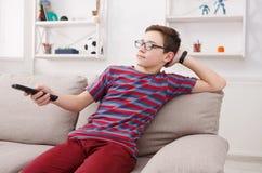 Televisión de observación del muchacho del adolescente, usando el telecontrol de la TV Imagen de archivo