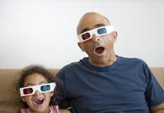 Televisión de observación del padre y de la hija en 3D Imagen de archivo libre de regalías