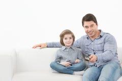 Televisión de observación del padre y del hijo junto en el sofá Foto de archivo libre de regalías