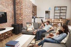 Televisión de observación del salón del plan de Sit On Sofa In Open de la familia Imágenes de archivo libres de regalías