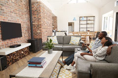 Televisión de observación del salón del plan de Sit On Sofa In Open de los pares fotos de archivo