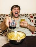 Televisión de observación feliz del hombre joven, comiendo las patatas fritas y dri Fotografía de archivo